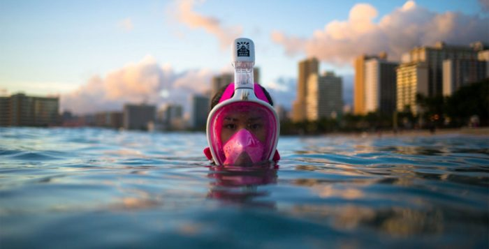 a woman with a snorkel mask on coming up from the water