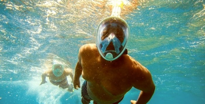 a man swimming toward the camera with a snorkel mask on