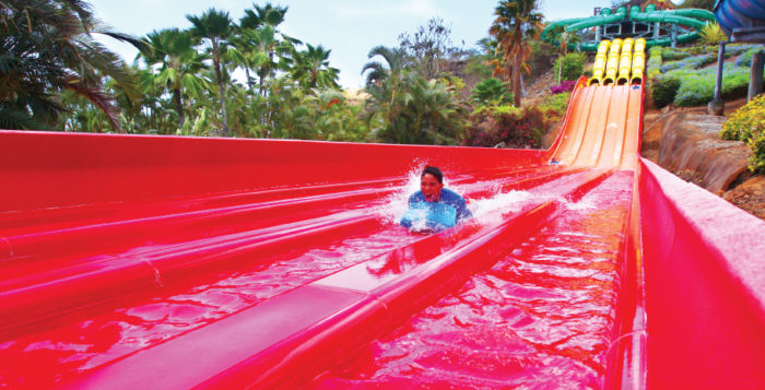 a man sliding down a red waterslide on a mat