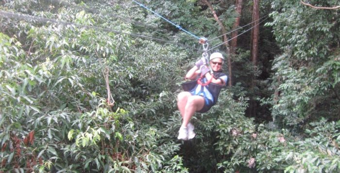 a woman zip lining through a rainforest