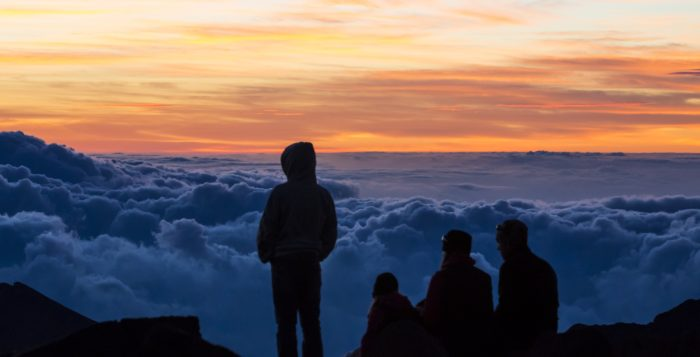 a person looking at sunrise atop haleakala