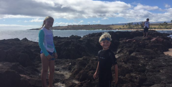 two children playing on lava rocks