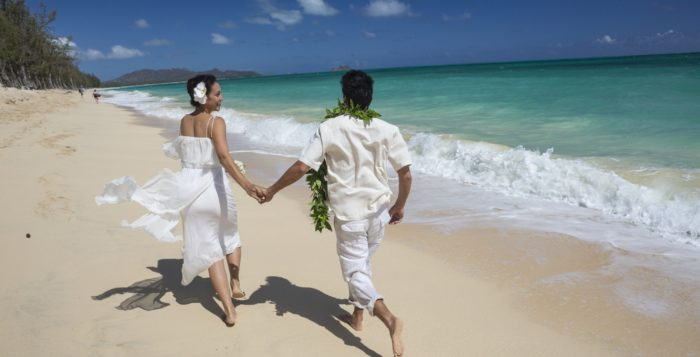 a couple running on a beach in wedding outfits
