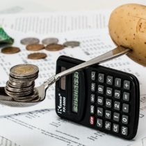 coins in a spoon and calculator