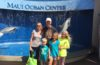 a family posing in front of the maui ocean center
