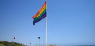 a rainbow flag on a beach