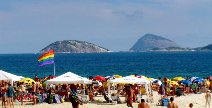 a beach with a rainbow flag and beachgoers on it