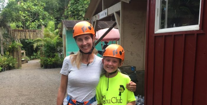 a woman and girl with ziplining equipment on