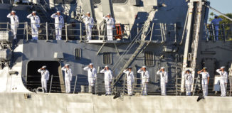 sailors saluting aboard a ship