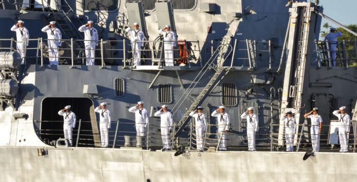 sailors saluting aboard a ship