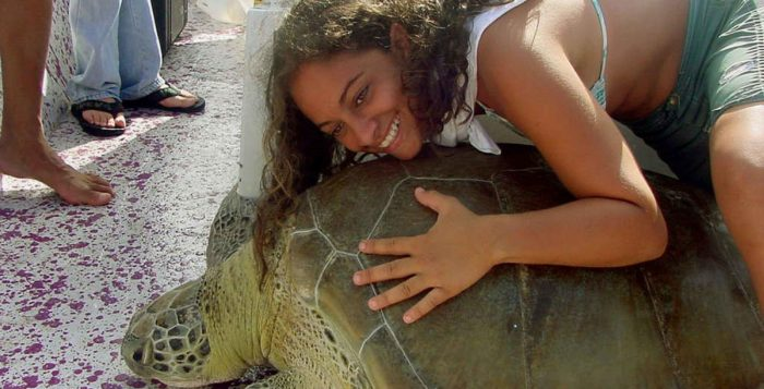 a girl laying on a sea turtle