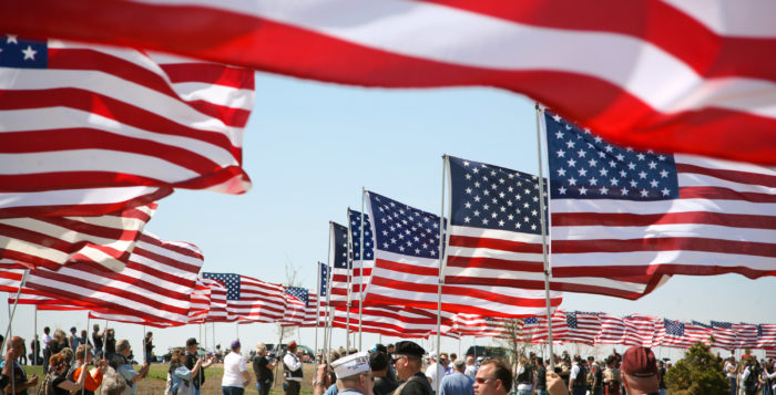 american flags waving over people