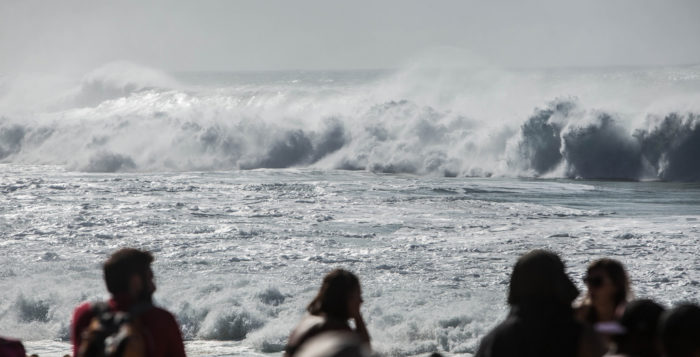 a crowd looks on at big waves
