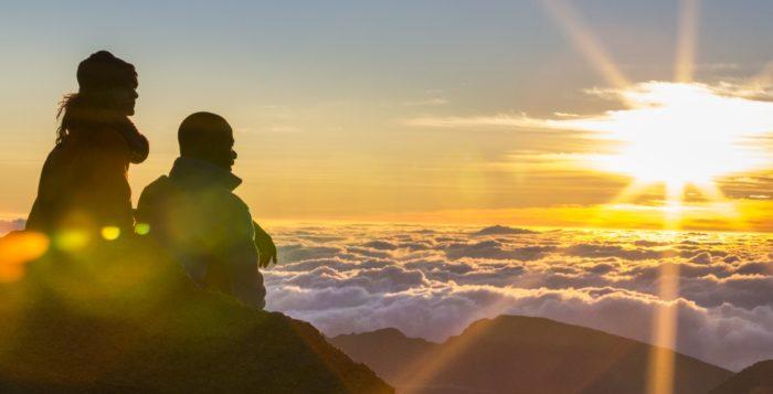 a couple watching the sunrise at haleakala national park