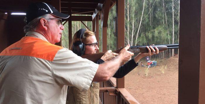 Person aiming gun at target