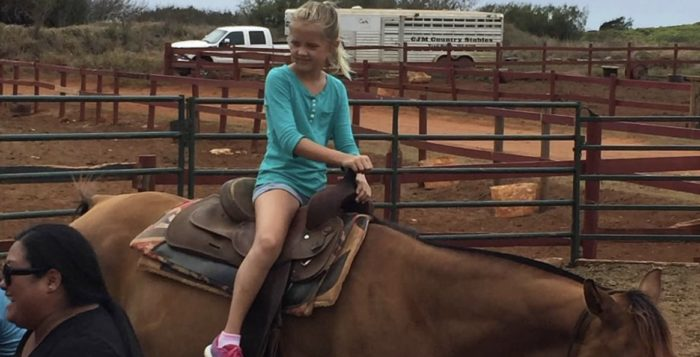 Girl sitting on a horse in a corral