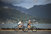 Kids cycling with Koolau's in background